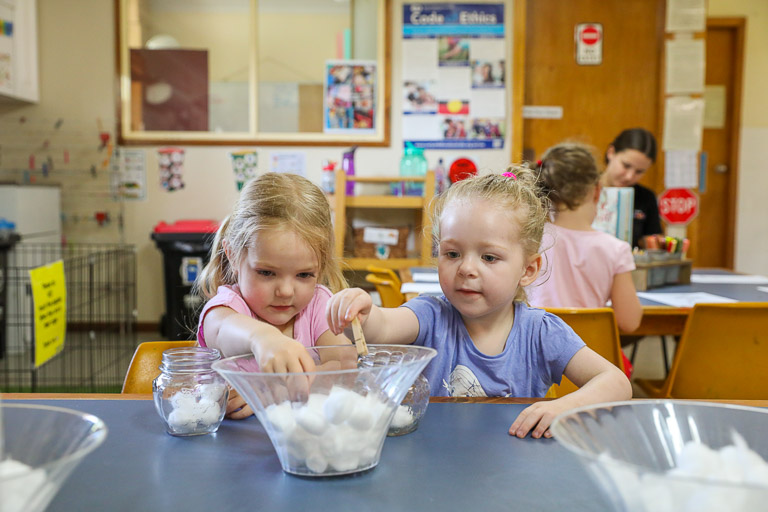Two little girls developing their fine motor skills at preschool